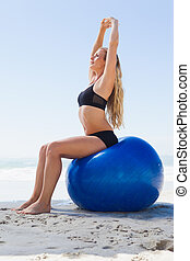 Fit blonde sitting on exercise ball at the beach on a sunny...