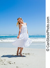 Pretty carefree blonde standing on the beach