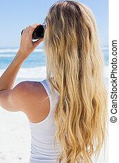 Blonde looking to the ocean through binoculars