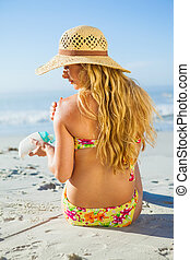 Gorgeous woman sitting on the beach in sunhat applying...