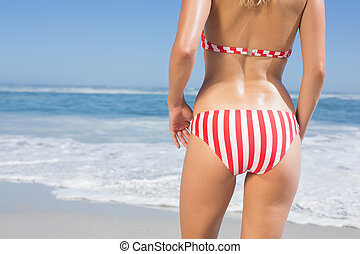 Mid section rear view of fit woman in striped bikini at...
