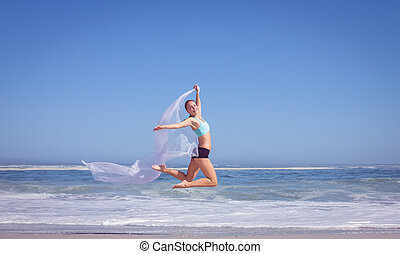 Fit woman jumping gracefully on the beach with scarf on a...