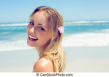 Beautiful blonde smiling at camera on the beach on a sunny...