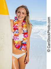 Smiling blonde surfer in white bikini and garland on the...