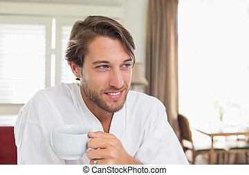 Handsome man having breakfast in his bathrobe drinking...