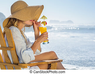 Smiling blonde relaxing in deck chair by the sea sipping...