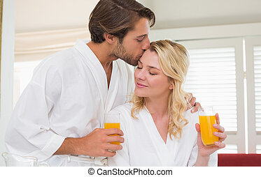 Cute couple in bathrobes drinking orange juice at home in...