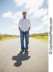 Handsome casual man standing on a road smiling at camera on...