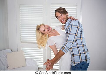 Cute young couple dancing together at home in the living...