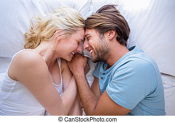 Cute couple relaxing on bed smiling at each other at home in...