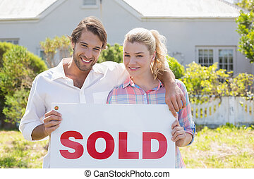 Cute couple standing together in their garden holding sold...