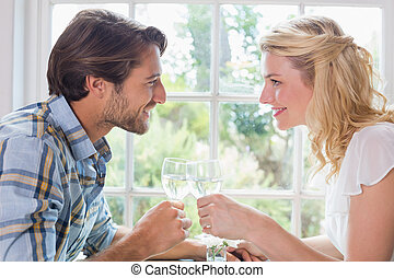 Cute smiling couple having a meal together at home in the...