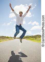 Handsome casual man leaping on a road smiling at camera on a...