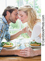 Cute affectionate couple having a meal together at home in...
