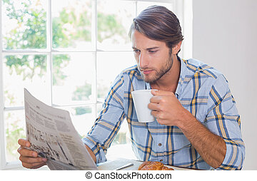Casual man having coffee while reading newspaper at home in...