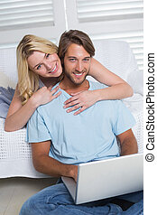 Happy casual couple sitting on couch using laptop smiling at...