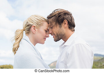 Cute smiling couple standing outside facing each other on a...