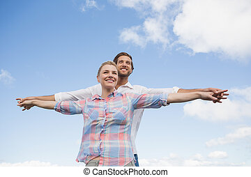Happy couple standing outside with arms stretched on a sunny...