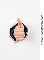 Thumbs up bursting through paper on white background