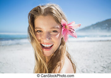 Beautiful smiling blonde with flower hair accessory on the...