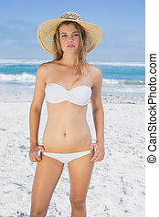 Beautiful blonde on the beach in white bikini and sunhat on...