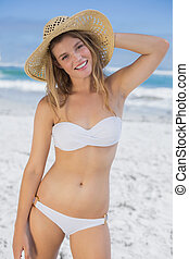 Beautiful happy blonde on the beach in white bikini and...
