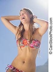 Laughing blonde in floral bikini on the beach on a sunny day