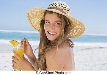 Pretty smiling blonde in bikini holding cocktail on the beach