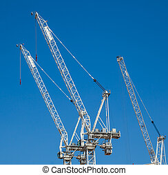 Under Constuction - Tall cranes building background concept