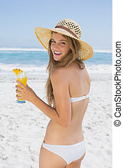 Smiling blonde in bikini holding cocktail on the beach