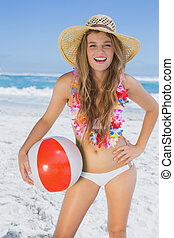 Fit smiling blonde in white bikini and straw hat holding...