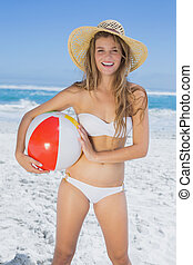 Fit blonde in white bikini and straw hat holding beach ball...