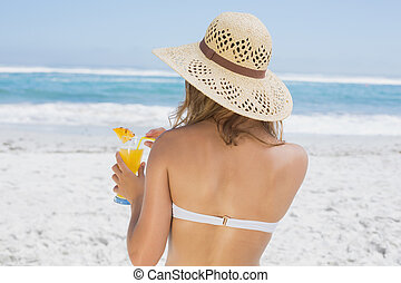 Woman holding cocktail on the beach on a sunny day