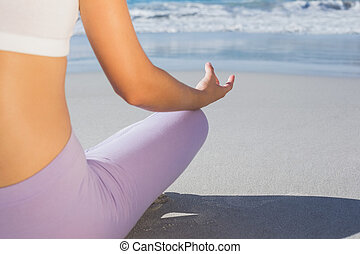 Sporty blonde sitting in lotus pose on the beach on a sunny...