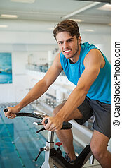 Smiling fit man on the spin bike at the gym