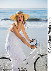 Beautiful blonde in white sundress on bike ride at the beach