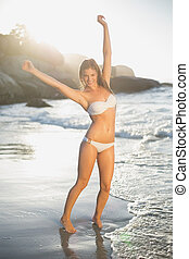 Beautiful smiling blonde in white bikini at the beach with...