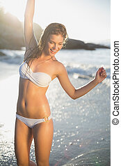 Beautiful laughing blonde in white bikini at the beach with...