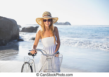 Beautiful smiling blonde in sundress with her bike at the...