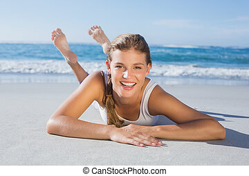 Sporty blonde lying on the beach sm
