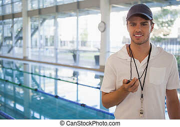 Swimming coach standing by the pool smiling at camera at the...