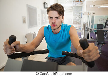Focused fit man on the exercise bike at the gym