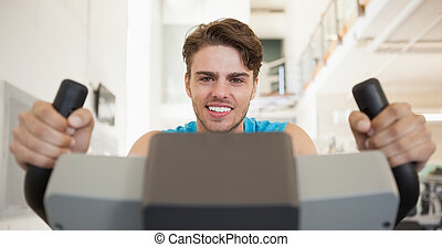 Smiling fit man on the exercise bike at the gym