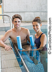 Man and woman standing with foam rollers in the pool at the...