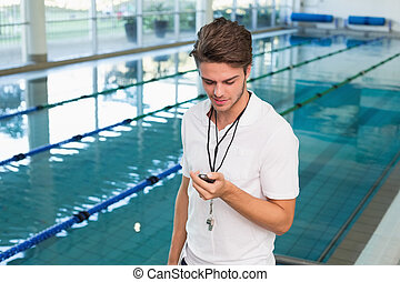 Swimming coach looking at his stop - Swimming coach looking...