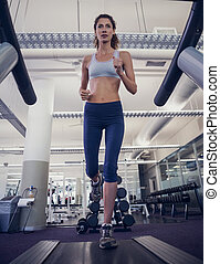 Fit woman running on the treadmill at the gym