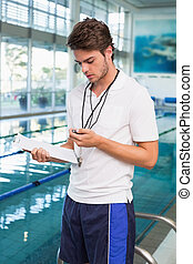 Swimming coach looking at his stopwatch by the pool at the...