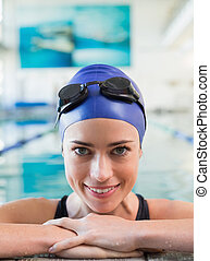 Fit swimmer in the pool smiling at