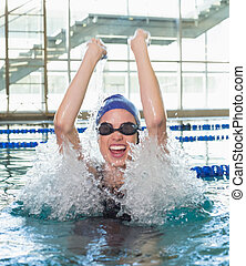 Excited swimmer cheering in the swimming pool at the leisure...