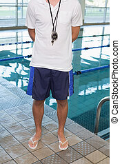 Swimming coach standing by the pool at the leisure center